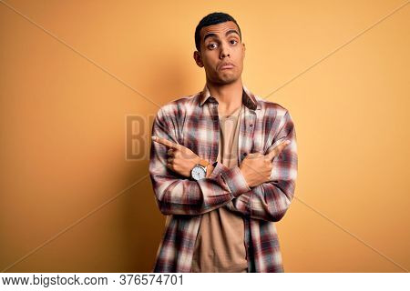 Young handsome african american man wearing casual shirt standing over yellow background Pointing to both sides with fingers, different direction disagree