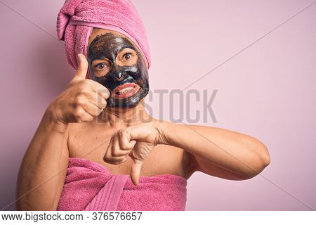 Middle age brunette woman wearing beauty black face mask over isolated pink background Doing thumbs up and down, disagreement and agreement expression. Crazy conflict