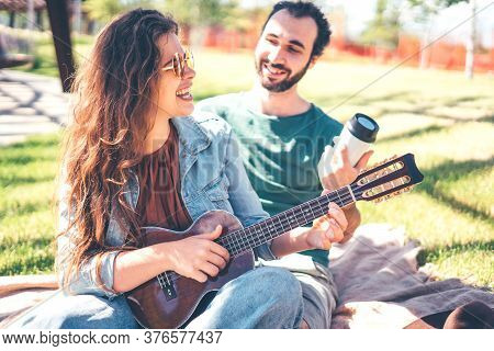 Yung Smiling Couple Enjoying Each Other On Picnic Day In The Modern Park. Teaches To Play Ukulele. L