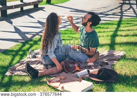 Beautiful Smiling Couple Enjoying Pizza On Picnic Day In The Park. Love And Fondness, Dating, Romanc