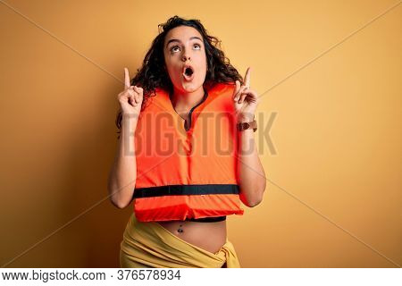 Young beautiful woman with curly hair wearing orange lifejacket over yellow background amazed and surprised looking up and pointing with fingers and raised arms.