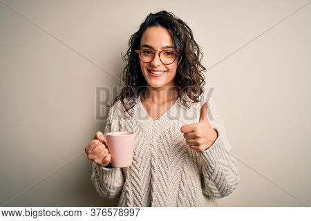 Young beautiful woman with curly hair drinking pink mug of coffee over white background happy with big smile doing ok sign, thumb up with fingers, excellent sign
