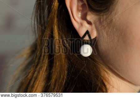 Close-up Of A Black And White Earring On A Woman's Ear. Earrings In The Form Of Geometric Shapes. Be
