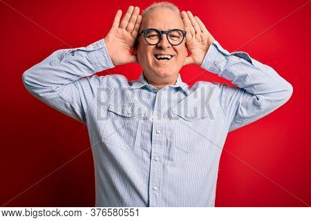 Middle age handsome hoary man wearing casual striped shirt and glasses over red background Smiling cheerful playing peek a boo with hands showing face. Surprised and exited