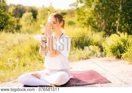 Young Woman Is Meditating In Lotus Position With Closed Eyes Sitting On Yoga Mat On Grass. Female Yo