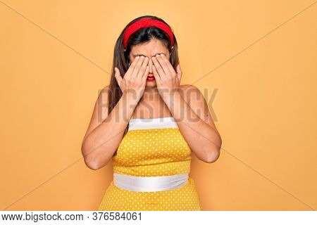 Young hispanic pin up woman wearing fashion sexy 50s style over yellow background rubbing eyes for fatigue and headache, sleepy and tired expression. Vision problem