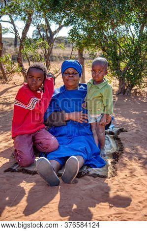 granny and kids, African family, sited in the yard of a village in Botswana