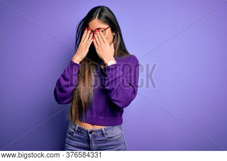 Young beautiful smart woman wearing glasses over purple isolated background rubbing eyes for fatigue and headache, sleepy and tired expression. Vision problem
