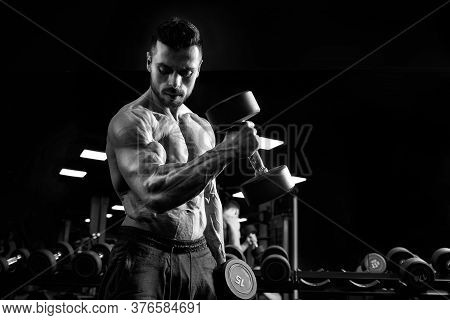 Side View Of Shirtless Male Bodybuilder Training Biceps With Dumbbell. Close Up Of Sportsman With Pe