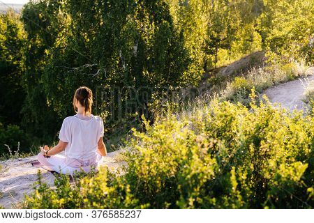 Rear View Of Unrecognizable Young Woman Meditating In Lotus Position Sitting On Top Of Rock Backgrou