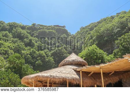Wooden Bungalow On White Sand Beach In Tropical Paradise. Wooden Cottage With A Reed Roof On The Isl