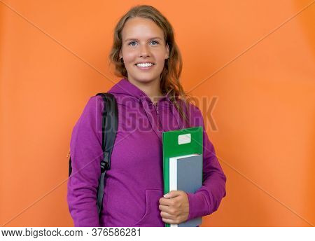 Beautiful Blond German Female Student With Hoody Isolated On Orange Background