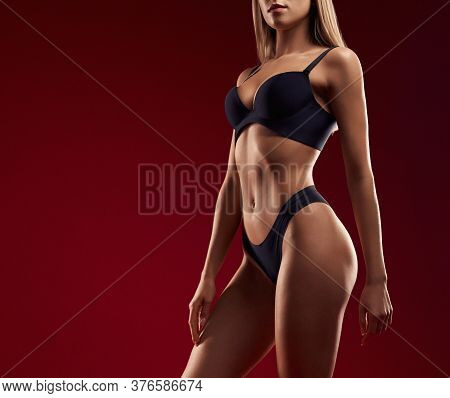 Side Crop Of Incognito Sexy Caucasian Female Model Wearing Black Lingerie Standing, Isolated On Dark