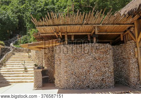 Reception Area With Reception Desk In A Beach Club. Stone Wall And Bamboo Roof