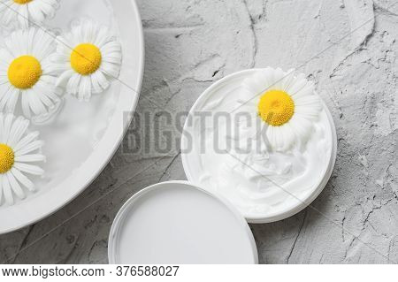Chamomile Natural Moisturizer. Chamomile In An Opened Jar With White Face And Body Cream. Plate With