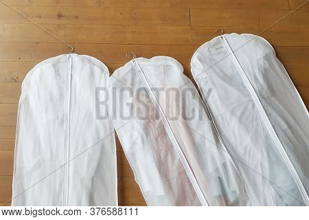 Three White Hanging Garment Bag On The Floor. The Morning Before The Wedding. Pack Your Things On A