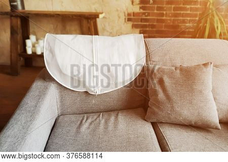 Wedding Dress In White Hanging Garment Bag On The Back Of The Couch. The Morning Before The Wedding.