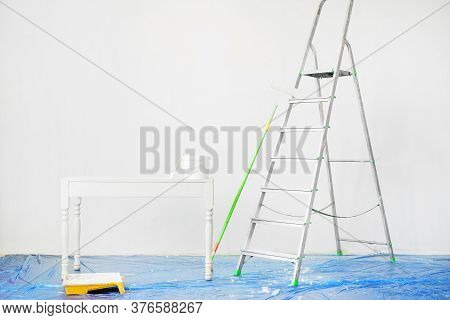 Tools For Painting Walls: A Stepladder, Roller, Tray, Bucket Of Paint, A Brush On The Floor With A P