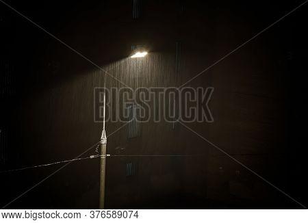 Heavy Rain Under Night Street Lamp Lights , Rainstorm, Grained Image.