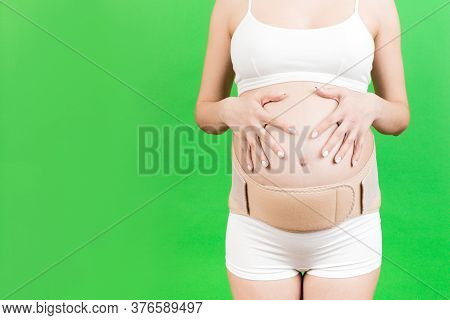 Cropped Image Of Pregnant Woman In Underwear Wearing Maternity Belt To Reduce Pain In The Back At Gr