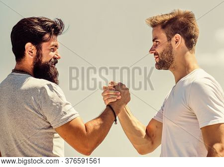 Handshake Arm Wrestling Style. Strong And Muscular Arms. Successful Deal Handshake Blue Sky Backgrou