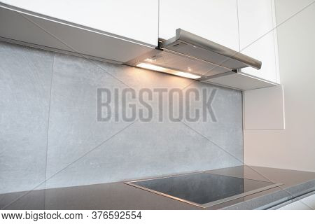 A Close-up On Under Cabinet Range Hood, Exhaust Vent Hood With Lights Working And Modern Electric St