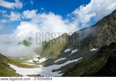 High Mountain Peaks Among The Clouds. Wonderful Summer Landscape Of Fagaras Ridge With Some Snow On