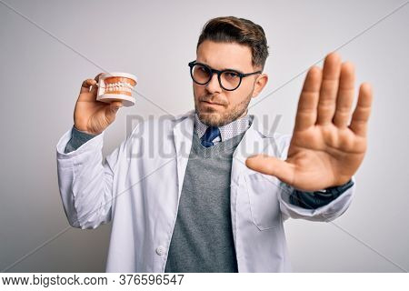 Young dentist man with blue eyes holding orthodontic dental prosthesis over isolated background with open hand doing stop sign with serious and confident expression, defense gesture