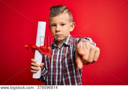 Young little caucasian student kid holding school degree over red isolated background pointing with finger to the camera and to you, hand sign, positive and confident gesture from the front