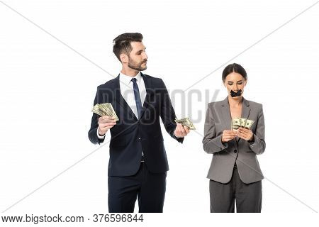 Businessman Holding Dollars And Looking At Businesswoman With Duct Tape On Mouth Isolated On White,
