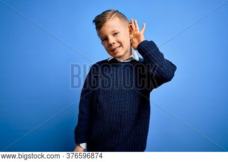 Young little caucasian kid with blue eyes wearing winter sweater over blue background smiling with hand over ear listening an hearing to rumor or gossip. Deafness concept.