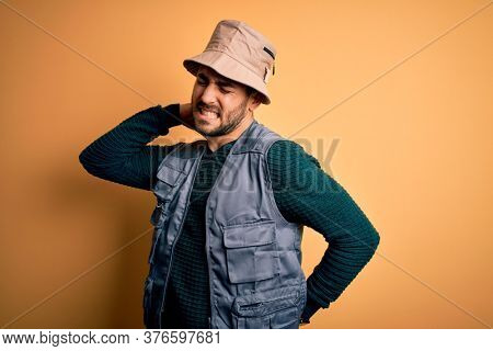 Handsome tourist man with beard on vacation wearing explorer hat over yellow background Suffering of neck ache injury, touching neck with hand, muscular pain