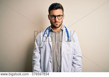 Young doctor man wearing glasses, medical white robe and stethoscope over isolated background skeptic and nervous, frowning upset because of problem. Negative person.