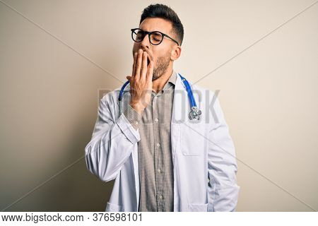 Young doctor man wearing glasses, medical white robe and stethoscope over isolated background bored yawning tired covering mouth with hand. Restless and sleepiness.