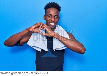 Young african american man wearing sportswear and towel smiling in love doing heart symbol shape with hands. romantic concept.