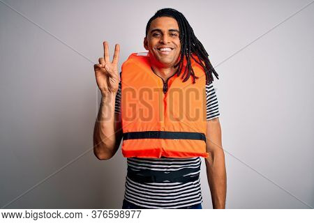Young african american afro man with dreadlocks wearing orange lifejacket smiling with happy face winking at the camera doing victory sign. Number two.
