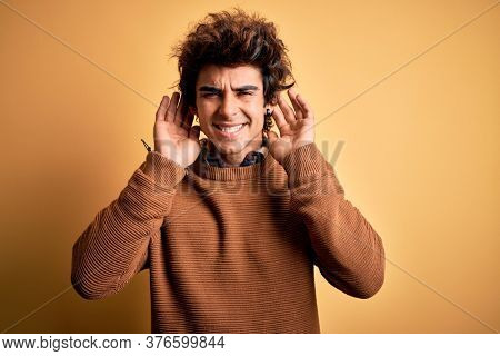 Young handsome man wearing casual shirt and sweater over isolated yellow background Trying to hear both hands on ear gesture, curious for gossip. Hearing problem, deaf