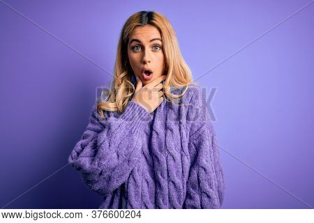 Young beautiful blonde woman wearing casual turtleneck sweater over purple background Looking fascinated with disbelief, surprise and amazed expression with hands on chin