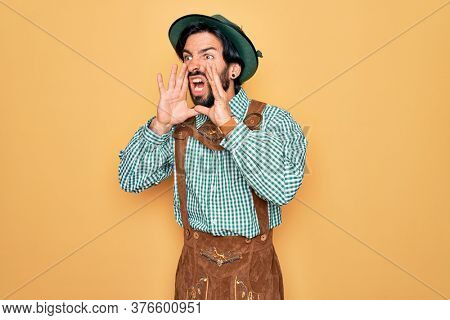Young handsome man wearing tratidional german octoberfest custome for Germany festival Shouting angry out loud with hands over mouth