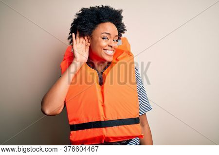 Young African American afro woman with curly hair wearing orange protection lifejacket smiling with hand over ear listening an hearing to rumor or gossip. Deafness concept.
