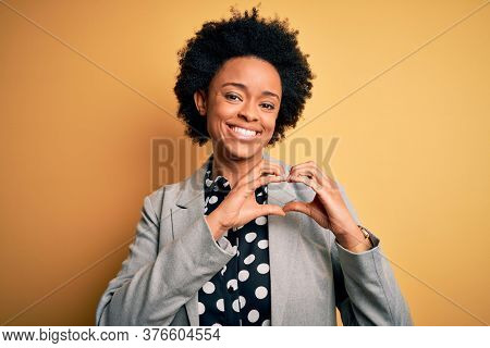 Young beautiful African American afro businesswoman with curly hair wearing jacket smiling in love showing heart symbol and shape with hands. Romantic concept.
