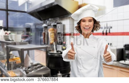 cooking, gesture and people concept - happy smiling female chef in toque showing thumbs up over restaurant or kebab shop kitchen background