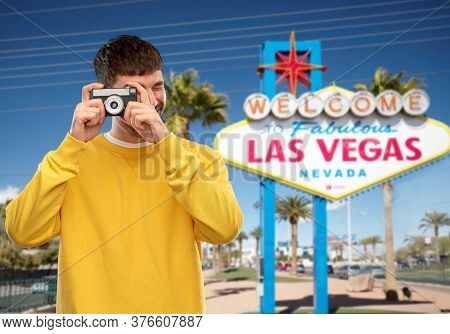 travel, tourism and photography concept - happy young male photographer in yellow sweatshirt taking picture with vintage film camera over welcome to fabulous las vegas sign background