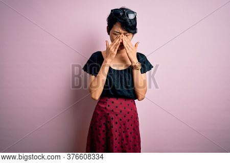 Young beautiful asian girl wearing casual dress standing over isolated pink background rubbing eyes for fatigue and headache, sleepy and tired expression. Vision problem