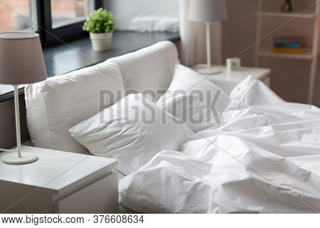 coziness and interior concept - cozy bedroom with white linen on bed