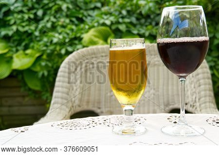 A Pint Of Beer And A Glass Of Red Wine Set Against A Green Plant, On White Table.