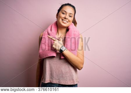 Young beautiful brunette sportswoman wearing sportswear and towel over pink background cheerful with a smile on face pointing with hand and finger up to the side with happy and natural expression