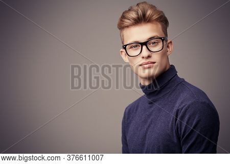 Male beauty. Portrait of a handsome young man with blond hair wearing glasses and look at camera. Optics for men.