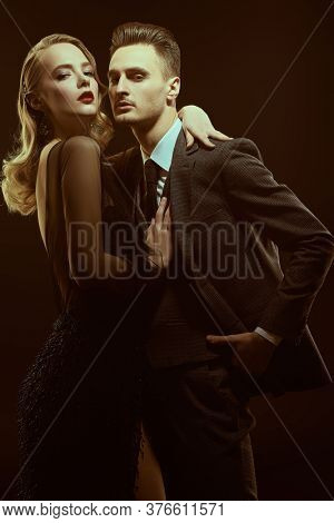 Beautiful passionate couple of man and woman in expensive evening dresses on a black background. Couple in love. Beauty, fashion.  Studio portrait.