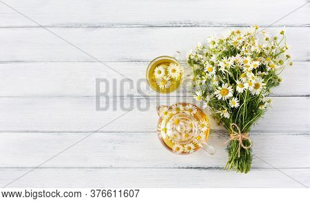 Chamomile Bouquet Tied With Twine, Glass Tearpot And Cup On White Wooden Background